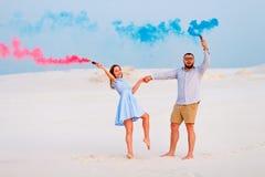 Potomstwa dobierają się pozycję na mienie barwiącej dymnej bombie, piasku, romantycznej parze z błękitnym kolorem i czerwonego ko Zdjęcia Royalty Free