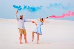 Potomstwa dobierają się pozycję na mienie barwiącej dymnej bombie, piasku, romantycznej parze z błękitnym kolorem i czerwonego ko Zdjęcie Stock