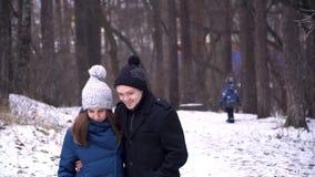 Potomstwa dobierają się przytulenie i całowanie w parku w zimie Portret piękna para ubierał w zimie odziewa w zdjęcia stock