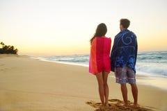 Potomstwa dobierają się ręczniki nad ramionami w plażowym piasku Zdjęcia Stock