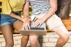 Potomstwa dobierają się robić zakupy online z laptopem i kredytową kartą podczas gdy siedzący na ławce w parku Obrazy Stock