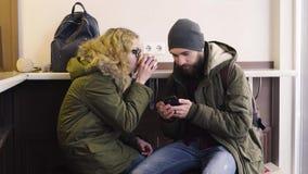 Potomstwa dobierają się używać smartphone obsiadanie w kawiarni w mieście zbiory
