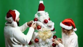 Potomstwa dobierają się ukwiecenia choinka w czerwonych kapeluszach na zielonym tle Nowego roku `s pojęcie zbiory wideo