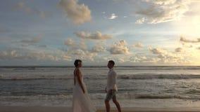 Potomstwa dobierają się w miłości chodzą w kierunku each inny przez plażę, spotkanie i całowanie, przy zmierzchem zbiory wideo