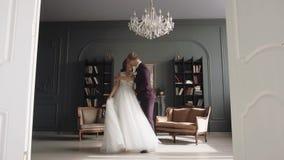 Potomstwa dobierają się w miłości kobiecie w ślubnej sukni w wnętrzu i mężczyźnie zdjęcie wideo
