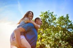 Potomstwa dobierają się w miłości ma zabawę w wiosny kwitnienia ogródzie Kobieta jedzie na jej chłopaka ` s plecy przy zmierzchem Zdjęcia Royalty Free