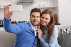 Potomstwa dobierają się wpólnie w domu weekendowego mienia smartphone bierze selfies obraz stock