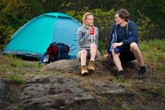 Potomstwa dobierają się wycieczkować z plecakami odpoczywa blisko namiotu w Zdjęcia Royalty Free