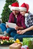 Potomstwa dobierają się z Święty Mikołaj kapeluszami robi zakupy online bożego narodzenia gif obrazy royalty free