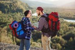 Potomstwa dobierają się z plecakami podróżuje wpólnie w górach Szczęśliwy modnisia mężczyzna całuje jego dziewczyny na wierzchołk zdjęcie stock
