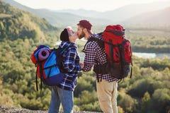 Potomstwa dobierają się z plecakami podróżuje wpólnie w górach Szczęśliwy modnisia mężczyzna całuje jego dziewczyny na wierzchołk obraz stock