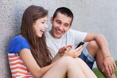 Potomstwa dobierają się z telefon komórkowy Zdjęcie Royalty Free
