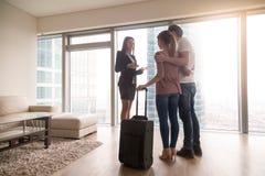 Potomstwa dobierają się z walizki spotkaniem z żeńskim pośrednikiem handlu nieruchomościami, wynajmowanie Obraz Royalty Free