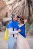 Potomstwa dobierają się zawijają w flaga Ukraina całują w jarze przeciw tłu drzewka palmowe i skały zdjęcia royalty free