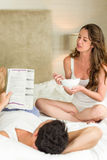 Potomstwa dobierają się czytelniczą gazetę i mieć śniadanie na łóżku Zdjęcia Stock