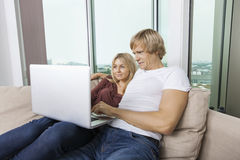 Potomstwa dobierają się używać laptop w żywym pokoju w domu Zdjęcie Royalty Free