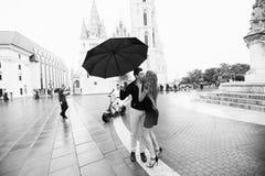 Potomstwa dobieraj? si? z parasolowym odprowadzeniem w Budapest na deszczowym dniu ch?opak dziewczyny ca?owania ogrodowa story cz obrazy royalty free