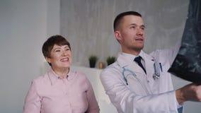 Potomstwa doc odwiedza pacjenta i dyskutują promieniowanie rentgenowskie zdjęcie wideo