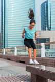 Potomstwa dostosowywali aktywnego kobiety ławki skoku kucnięcia doskakiwanie na miasto ulicie Sprawności fizycznej dziewczyna rob Fotografia Stock