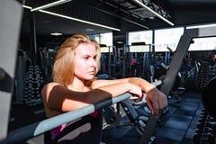 Potomstwa dostosowywali kobiety pozycję przy gym przed barbell femaleness fotografia stock