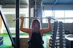 Potomstwa dostosowywali kobiety przy gym robi pulldown ćwiczeniu z ciężarem m obraz stock