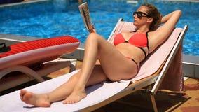 Potomstwa, eleganckiej kobiety czytelnicza książka dalej sunbed basenem zdjęcie wideo