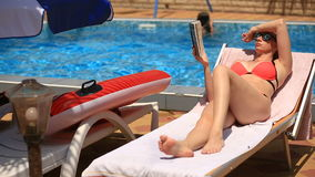 Potomstwa, eleganckiej kobiety czytelnicza książka dalej sunbed basenem zbiory wideo