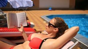 Potomstwa, eleganckiej kobiety czytelnicza książka dalej sunbed basenem zbiory