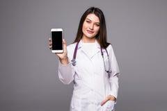Potomstwa fabrykują kobiety wskazuje na telefonu komórkowego ekranie na popielatym tle fotografia stock