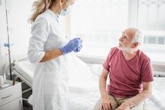 Potomstwa fabrykują w ochronnej masce opowiada z pacjentem obrazy stock