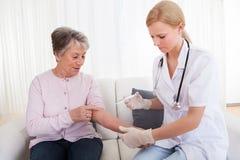 Potomstwa fabrykują wstrzykiwanie szczepionki starsza kobieta Zdjęcia Stock