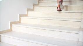 Potomstwa garbnikujący żeńscy cieki w sandałach iść w górę schodków zbiory