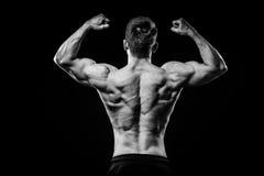 Potomstwa i dysponowana bodybuilder atleta demonstrują bicepsa tylnego widok na czarnym tle Obraz Stock