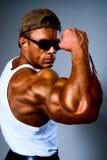 Potomstwa i dysponowany samiec model pozuje jego mięśnie Zdjęcie Stock