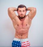 Potomstwa i dysponowany samiec model pozuje jego mięśnie Zdjęcia Stock
