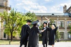 potomstwa kończyli studia uczni z dyplomami wita each inny zdjęcia stock