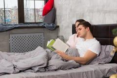 Potomstwa koncentrujący dobierać do pary czytelnicze książki podczas gdy kłamający w łóżku, ou zdjęcie royalty free