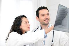 Potomstwa lekarka i pielęgniarka analizuje prześwietlenie obrazy royalty free