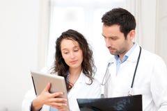 Potomstwa lekarka i pielęgniarka analizuje prześwietlenie fotografia stock