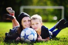 Potomstwa macierzyści i jej chłopiec bawić się mecz piłkarskiego na pogodnym letnim dniu Fotografia Royalty Free