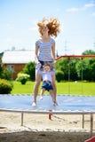 Potomstwa macierzyści i mała córka odbija się na trampoline fotografia royalty free