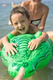 Potomstwa macierzyści i uśmiechnięty chłopiec syn w zielonej baseball nakrętce bawić się w morzu w dnia czasie Pozytywne ludzkie  zdjęcie royalty free