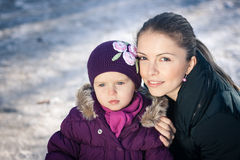 Potomstwa macierzyści na śnieżnym zima dniu outdoors i jej dziewczynka Obraz Stock