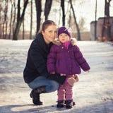 Potomstwa macierzyści na śnieżnym zima dniu outdoors i jej dziewczynka Zdjęcia Royalty Free