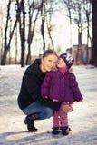 Potomstwa macierzyści na śnieżnym zima dniu outdoors i jej dziewczynka Obraz Royalty Free