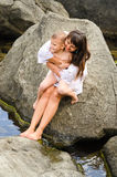 Potomstwa macierzyści i jej syna obsiadanie na skale Zdjęcia Royalty Free
