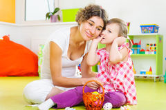 Potomstwa macierzyści i mała córka maluje Wielkanocnych jajka Fotografia Stock