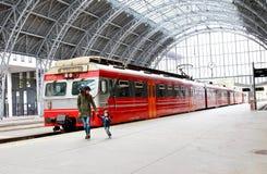 Potomstwa matki i małe dziecko spacer przez Bergen dworca platform z typowym czerwonym Voss trenują na tle, Bergen obraz stock