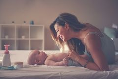 Potomstwa matkują bawić się z jej chłopiec w łóżku Macierzysty cieszy się i Fotografia Stock