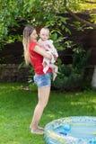 Potomstwa matkują brać jej chłopiec z nadmuchiwanego basenu po sw Zdjęcia Stock